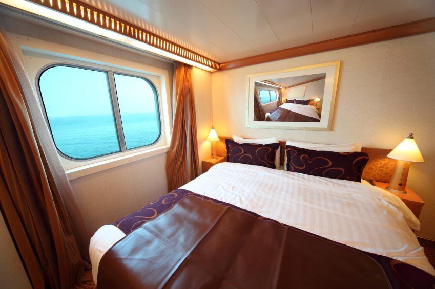 ship cabin with big double bed and window with view on sea summe